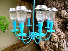 Make a cute solar powered outdoor chandelier for your backyard. Use a thrift sto Make a cute solar powered outdoor chandelier for your backyard. Use a thrift store find or an old light fixture for the DIY project. Home Jelly shows you how. Diy Solar, Solar Light Crafts, Solar Light Chandelier, Outdoor Chandelier, Diy Chandelier, Chandeliers, Painted Chandelier, Solar Lamp, Pendant Lights