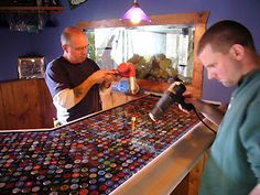 Mancave epoxy bar top made with beer labels coasters for Beer cap bar top