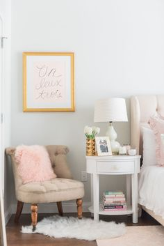 Blogger Jessica Sturdy of Bows & Sequins shares her Chicago Parisian-chic bedroom design. Blush pink rug, Un Deux Trois blush pink print, tufted linen chair, white faux shag animal skin rug, white round nightstand, white glass gourd lamps.