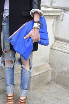 haha My body just melted.. I love this outfit... the ripped destroyed jeans with the wayy over sized clutch. and its brighttt blue!