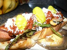 Grilled Hot Dog on Toasted Italian Bread with Peppers, Onions, Mushrooms,  Marinara,  Italian Cheeses, and Peperoncici.