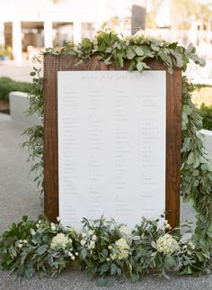 Tall wooden sign with gorgeous natural garland: http://www.stylemepretty.com/2015/03/19/rustic-and-elegant-tampa-yacht-club-wedding/ | Photography: Justin DeMutiis - http://justindemutiisphotography.com/