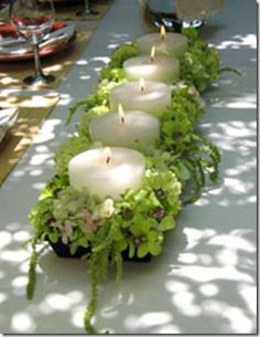 Short and stout candles in container filled with green amaranthus, orchids and hydrangea.
