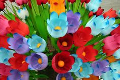 Hold onto your hats, folks! These BEAUTIFUL flowers are made from . . . drum roll please . . . PLASTIC SODA BOTTLES! Brilliant!