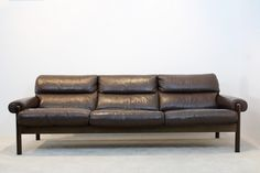 This chocolate brown Scandinavian leather three-seater sofa features leather…