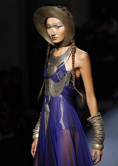 "French designer Jean-Paul Gaultier styling for his Haute Couture Spring Haute Couture Collection Summer 2010 collection presented in Paris, January 27, 2010.  Amazing juxtaposition between the heavy geometric metalwork and the light and airy dress. The ""helmet/mask"" looks especially uncomfortable."