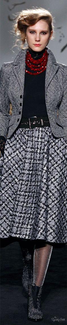 Roccobarocco F-16 RTW: black turtleneck top, necklace, herringbone jacket, midi skirt.