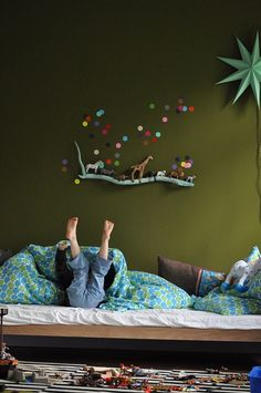 I just love the wall decoration: that branch with the animals and those cute little dots! So creative and it adds such a wonderful touch of whimsy to this child's room. It would be equally cute on a nursery wall out of reach from tiny hands-especially with small parts.