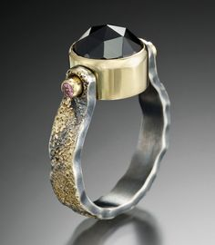 JENNY REEVES -  Cobblestone pattern band in Argentium sterling silver and 18K gold, with rose cut black spinel and faceted pink tourmaline in kinetic setting.  Fabricated, oxidized.