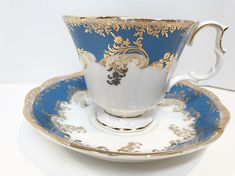 Royal Albert Bone China of England crafted this elegant blue and gold teacup and saucer. It is part of the Regina Series, namely the Aquamarine pattern. This lovely tea cup and saucer is a blue, not an aqua. The pattern name might be a little misleading. Royal Albert is a very popular