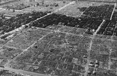 After an incendiary bombing, a view of some of the damage in Tokyo, Japan in 1945. A strip of residential buildings remains undamaged, surrounded by ashes and rubble of neighboring structures burned or blasted to the ground.
