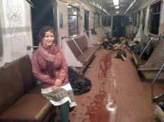 A young Russian woman poses happily and calmly in front of a pile of dead bodies. The bodies were dragged to the end of the train and are victims of the 2010 Moscow metro bombing where over forty people were killed and over a hundred injured.