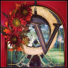 Fall wreath made with Hobby Lobby materials. So easy! All you need is a blank wreath, floral arrangement and letter. Use pliers to strip the stems down to the wire and push them into the wreath.