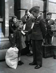 London, 10th September, 1942: Young Brian Lee wearing his RAF uniform, studies the evacuation label on fellow evacuee Alice King, aged 5, from Rotherhithe, Kent, whilst waiting on the platform at London's Euston station. (Photo by Popperfoto/Getty Images)
