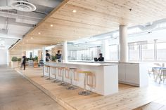 This remodelled office interior by Atelier Pierre Thibault is divided by a long wood-clad walkway, dotted with spaces for vegetation and socialising.