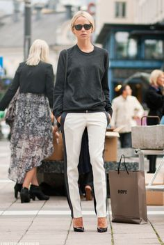 Minimalist chic in black stripe trousers, a crewneck sweater and black pumps