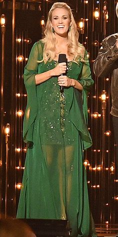 Carrie Underwood's 11 Glam CMA Looks | GYPSY WOMAN | We didn't expect Carrie to revert to caftans this early in her pregnancy, but she looks so glam in hers, she kinda makes us want one of our own. The star accents her sparkly emerald Randi Rahm number with matching earrings and a half-up do.