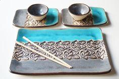 Un arte original para servicio de sushi - este listado está para un conjunto de cerámica servicio de 5 piezas que incluye una placa grande, dos pequeños platos y dos tazas de salsa de soja.  Se trata de una boda o fiesta regalo fantástico para alguien especial que disfruta de la comida. Este conjunto ha sido formado de arcilla blanca y cubierta esmalte gris y turquesa. Decoración de encaje bronce oro.  Tamaño aprox: Plato grande 12 x 7 2 pequeñas placas de 4.5 x 7 Platos de soja (cuencos) 3…