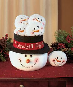 Snowball Fun Decoration A smiling snowman head has an opening on its top hat that's filled with 5 little snowballs. The Lakeside Collection