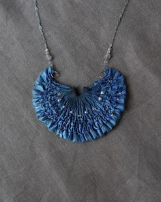 STAR DIADEM  £95.00  In this necklace is I see the shape of a boat sailing through lapping waves, through the evening sky, navigating by the constellations, reaching for a celestial crown set with glimmering diamonds.    The silk is dyed a lovely indigo blue with a hazy, raw hem like a water's edge. It is pleated, smocked and beaded with a variety of glass beads. More faceted beads embellish the chain.