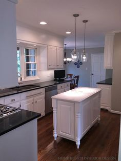 "Pretty Remodeled Kitchen without changing cabinets or floor plan footprint. B.M. White Dove paint on cabinets, DuPont Zodiaq ""Galaxy Black"" quartz count tops, backsplsh tile is Nanda 3x6 in ""Soft White"", pulls by Liberty from Home Depot, walls are B.V. Hazy Skies, custom island with Caesarstone ""Frosty Carrina"" countertop, glass pendants from Lowe's"
