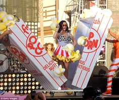 Making her mark: Perry bursts out of a popcorn packet in a movie themed dress complete with film reel bra and waistband and a giant popcorn skirt during her on-stage performance