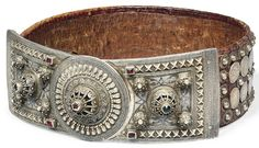 A LARGE OTTOMAN SILVER-MOUNTED BELT, OTTOMAN TURKEY OR CAUCASUS, DATED AH 1278/1861-2 AD Formed of two rectangular panels and a central disk, the hinge concealed on the reverse, the decoration with applied silver filigree bosses, the borders with embossed cross-motif bands, surrounded with fine filigree and granulated work