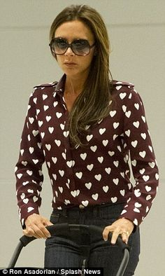 Looks familiar: Victoria stepped out in a Burberry blouse similar to Harry Styles favourite £350 heart-print navy blue number from Burberry