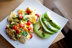 Egg scramble with onion, tomato, parsley and salt & pepper sided with half an avocado and lemon juice.