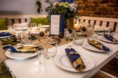 Rustykalne, granatowo - złote jesienne wesele. Biało-niebieskie kwiaty w słoiku z koronką, obok menu, ekologiczny bieżnik, złote liście, szyszki, żołędzie i kamyczki. Na talerzach sztućce w złotych i granatowych serwetkach, obwiązane sznurkiem z koronkową kokardką. / Rustic, wedding, natural, eco, table, decoration, fall, autumn, ideas, white, gold, navy, blue, flower, centerpieces, rocks, cones, acorns, leaves, candles, mason jar, lace, table number, menu, napkins, place setting, bow.