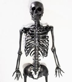 on a high-frequency vibrating table planted in the jack fischer gallery lies a life-sized skeleton made of solid graphite by artist agelio batle.