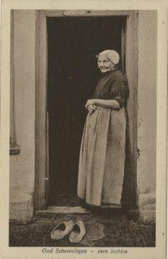 ...Holland -- Oude Scheveningse vrouw in dracht schept een luchtje voor haar huisje. ca 1915 J. van der Markt, Scheveningen, nr. 23560...