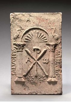"""A LARGE BYZANTINE DEDICATORY TERRACOTTA RELIEF TILE FOR BISHOP MARCIANUS MID-7TH CENTURY A.D.  Rectangular, with moulded decoration comprising a central Chi-Rho flanked by Alpha and Omega, two rosettes at the base, with two columns on either side surmounted by a semicircular arch decorated with shell motif, the arch flanked by two dolphins, an inscription on the left reads """"SALVO EPIS[COPO]"""" and on the right """"MARCIANO"""", repaired 15½ in. (39.5 cm.) high"""