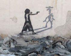 street-art-graffiti-painting-iran-boy-gun-fight-shoot-don-quixote-windmills-rubble