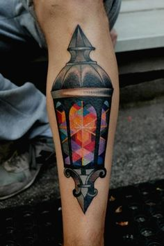 Marcin Surowiec tattoos an antique street lamp with cubist colors in this artistic vintage tattoo