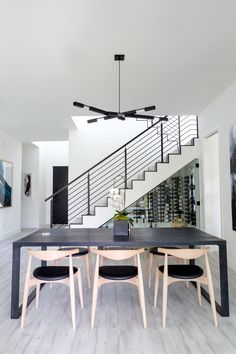 The table is a custom-charred oak wood dining table with a powder coated steel base by Harington Garnero. The dining chairs are the Hans J. Wegner CH 20 Elbow Chair.