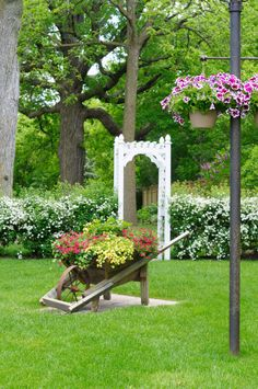 Large wooden wheel barrow with metal wheel in large grassy area loaded with red and yellow flowers.