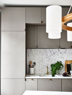 Corduroy-ish cabinets + marble backsplash in the kitchen of photographer Marcus Ohlsson & fashion designer Natalia Altewai's Stockholm apartment.