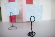 DIY Wire place card holders are easy to make and will cutely display your table numbers or labels. They could even hold photos that may be lying around to whimsically line a mantel or dinning table at home. See more party and wedding decor at http://pinterest.com/wineinajug/party-wedding-decor/