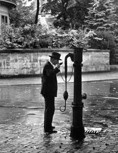 A man drinking water at a well pump. Photograph by Alfred Eisenstaedt. Frankfurt, Germany, 1931.