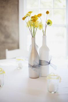 White wine bottle with ocean blue ribbons. Flowers out of the top need to be purple, blue, or white (babies breath)