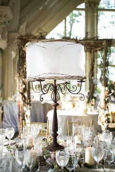 Try unique centerpieces for rustic weddings - like this custom lamp comprised of candelabrum decorated with twigs ~ https://www.insideweddings.com/weddings/east-coast-countryside-wedding-with-vintage-details/521/