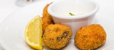 Fried conch fritters as appetizer with sauce and lemon wedge