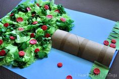Toilet paper tube cut in half, tissue paper, and buttons make a really cute apple tree craft!