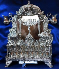 Our Antique Russian silver ornate oil Chanukah Menorah, made in Warsaw, 1891 by Antoni Riedel. Spectacular and unique. Includes central menorah, sceptres, crown supported by lions, resting stag at apex, nesting doves on palm trees, angels holding a low garland fence, higher chain fence with an eagle and stags on fence posts. Two shabbat lamps double as oil pitcher and Shamash. 8 Chanukah lamps also shaped as pitchers. Silver music box plays waltz (possibly Haneirot Halalu).