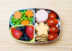 blanched peas and carrot flowers, blueberries and strawberries, sesamee and rice crackers, cheese  and uncured ham flowers, cherry tomatoes.