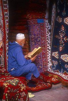 Carpet seller reading - Marrakech, Morocco