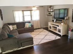 Farmhouse decor, farmhouse style, living room decor, split level living room, open concept, gray sectional, floating shelves, farmhouse living room, modern farmhouse, hardwood floors, white tv console, white rug, tv room, family room Instagram - @rocknrob