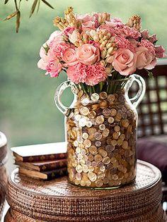 Um recipiente menor com água foi colocado dentro da ânfora de vidro para acomodar o buquê de rosas tipo gloss e spray, cravos e angélicas. Por fora, botões de madrepérola