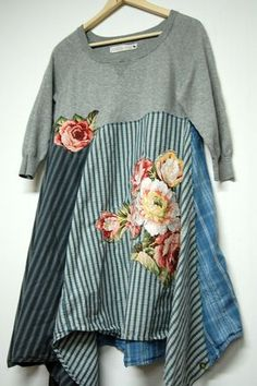 This unique boho chic style tunic dress s constructed of cotton panels in shades of blue and gray creatively stitched to a soft gray sweater. Adorned on front and back with beautiful rose appliques. Wear it alone as a dress or over jeans or leggings as a long tunic.  Fits up to Womans size Large  Approximate Measurements: Bust- to 40 Length from shoulder to hem- varies 33 to 44  Care: Machine wash delicate. Tumble dry low  All Primitive Fringe garments are pre-washed then inspected to check…